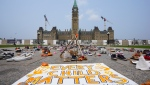 A memorial on Parliament Hill continues to be displayed in Ottawa on Monday, July 19, 2021, as the number of possible grave sites raises at residential schools across Canada. THE CANADIAN PRESS/Sean Kilpatrick