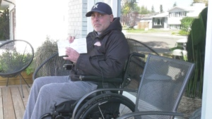 Mark Sikorski holds a voter card which says his neighbourhood polling station met accessibility criteria. (Carla Shynkaruk/CTV News)