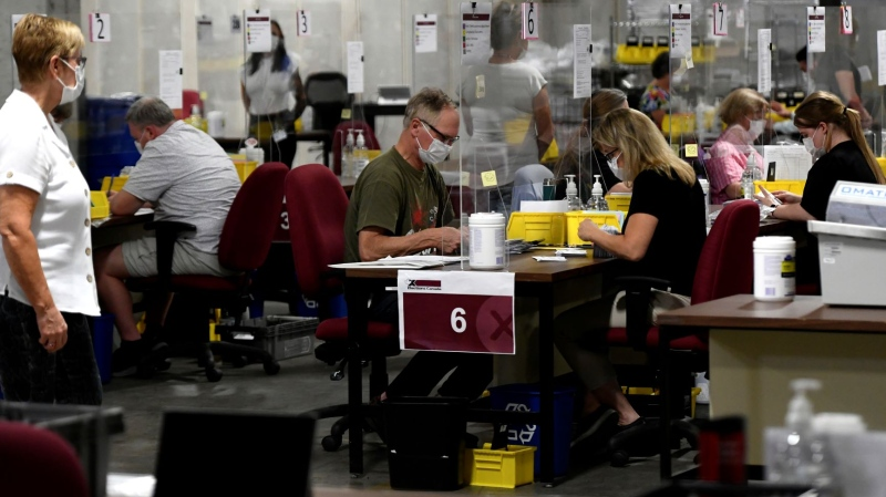 Special ballot officers count special ballots from national, international, Canadian Forces and incarcerated electors at Elections Canada's distribution centre in Ottawa on election night of the 44th Canadian general election, on Monday, Sept. 20, 2021. THE CANADIAN PRESS/Justin Tang