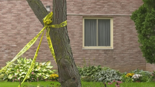 Yellow police tape is wrapped around a tree outside an apartment building in Collingwood, Ont., on Tues., Sept. 21, 2021 (Katelyn Wilson/CTV News)