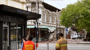 Emergency workers survey damage in Melbourne, Australia, where debris is scattered on a road after part of a wall fell from a building during an earthquake, Wednesday, Sept. 22, 2021. (James Ross/AAP Image via AP)