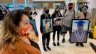 Tataskweyak Cree Nation members hold pictures of youth in the community who have died by suicide, as they greet Rylee Nepinak who returned to Winnipeg after a cross-Canada ride to raise awareness of the mental health crisis in the community. (Source: Scott Andersson/CTV News Winnipeg)