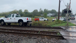 CN Rail trucks are parked near the rail crossing at Coronation Boulevard in Amherstview, Ont., near where a rail car derailed Wednesday, Sept. 22, 2021. No one was hurt. (Kimberley Johnson / CTV News Ottawa)
