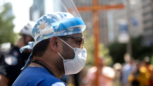 A healthcare professional watches as demonstrators gather outside Toronto General Hospital, on Monday September 13, 2021, to protest against COVID-19 vaccines, COVID-19 vaccine passports and COVID-19 related restrictions. THE CANADIAN PRESS/Chris Young