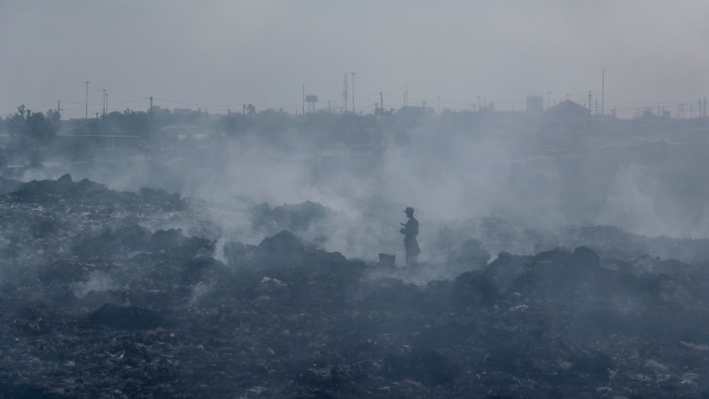 In this Tuesday, Sept. 7, 2021 file photo, a man who scavenges recyclable materials for a living walks across a mountain of garage amidst smoke from burning trash at Dandora, the largest garbage dump in the capital Nairobi, Kenya. (AP Photo/Brian Inganga, File)