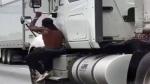 Video shows random man holding onto semi-trucks