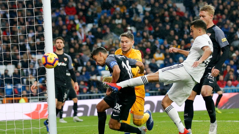 Real Madrid's Sergio Reguilon, right, tries to score during the La Liga soccer match between Real Madrid and Sevilla at the Bernabeu stadium in Madrid, Spain, Saturday, Jan. 19, 2019. (AP Photo/Andrea Comas)