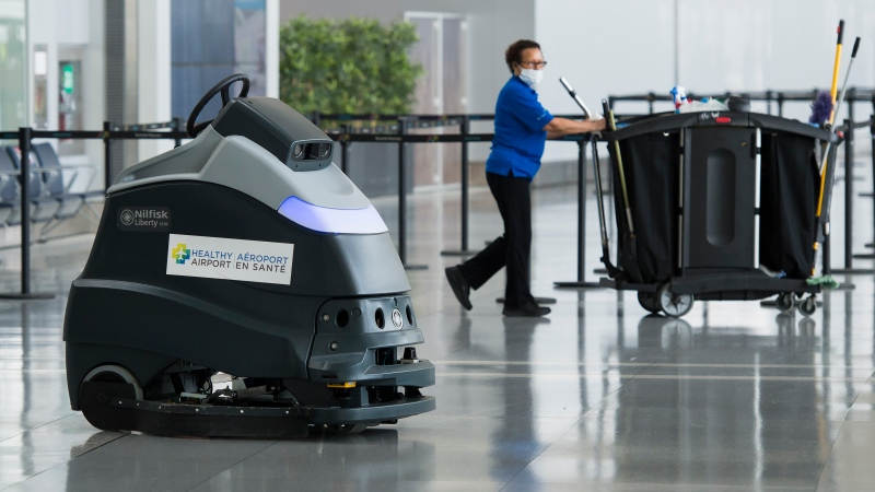 A automated floor cleaner that sanitizes the floor is shown as a worker walks by at Pearson International Airport during the COVID-19 pandemic in Toronto on Tuesday, June 23, 2020. THE CANADIAN PRESS/Nathan Denette