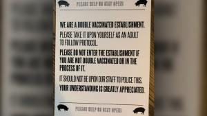 A sign at a location of The Pig and Duke in Calgary notifying patrons of the pub's willingness to comply with, but unwillingness to police, the rule that only double vaccinated clients may enter.
