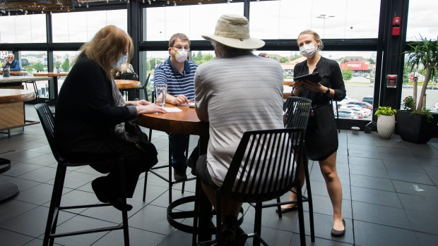 Patrons sit on the patio as a waitress takes orders in Toronto on Wednesday, June 24, 2020.THE CANADIAN PRESS/Nathan Denette