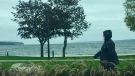 A woman walks along Barrie's waterfront on a cool, rainy day. (CTV News Barrie)