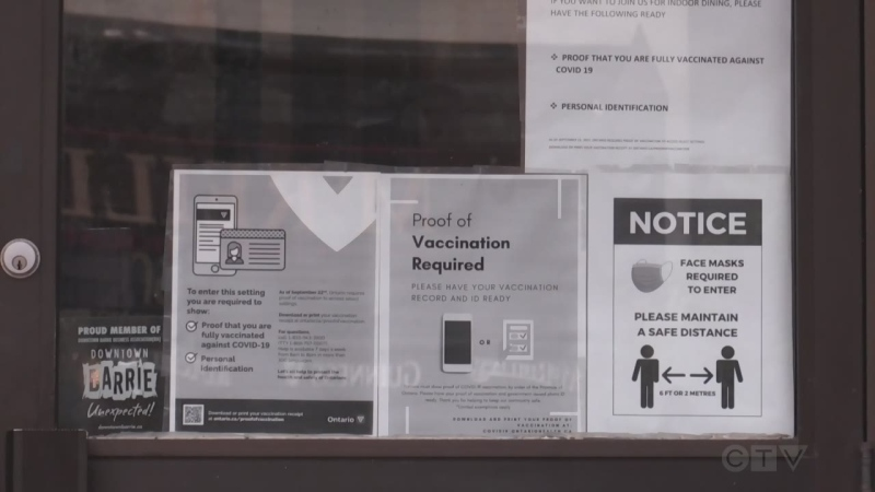 A downtown Barrie, Ont., business posts a sign on its entry that requires customers to show proof of vaccination. (Craig Momney/CTV News)