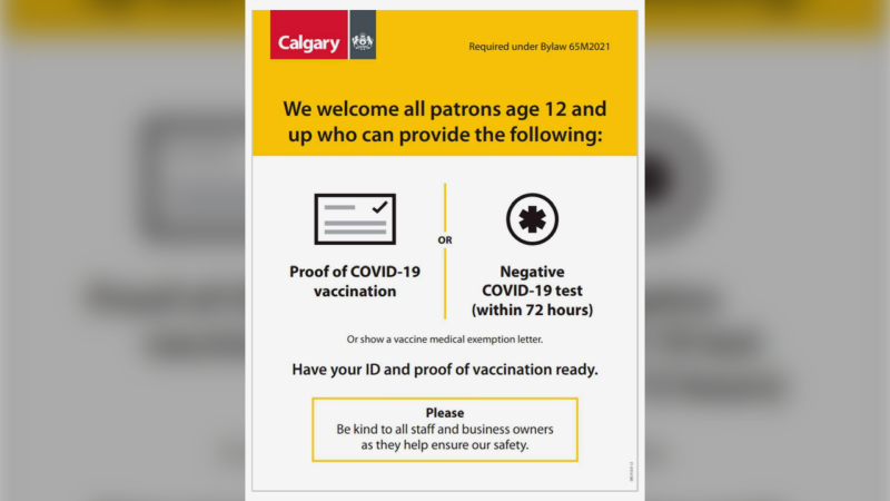 A City of Calgary sign warns people must have proof of vaccination or a negative COVID-19 test to enter.