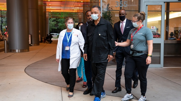 The Rev. Jesse Jackson, centre, joined by Dr. Leslie Rydberg, left and physical therapist Talia Shapiro, right, is released from therapy at the Shirley Ryan AbilityLab where he spent nearly a month recovering from COVID-19, Wednesday, Sept. 22, 2021. (E. Jason Wambsgans/Chicago Tribune via AP)