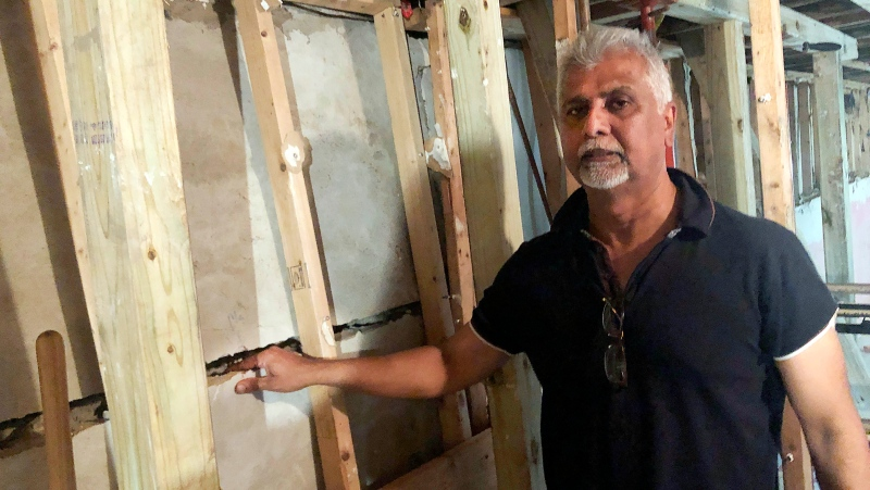 Sahadeo Bhagwandin shows a wide crack in the wall of his basement, in the Queens borough of New York, Friday, Sept. 17, 2021. (AP Photo/Bobby Caina Calvan)