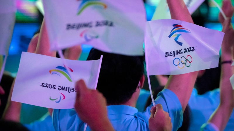 Participants wave flags with the logos of 2022 Beijing Winter Olympics and Paralympics before a launch ceremony to reveal the motto for the Winter Olympics and Paralympics in Beijing, on Sept. 17, 2021. (Mark Schiefelbein / AP)