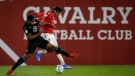 Pacific FC's Terran Campbell, left, and Cavalry FC's Jose Escalante battle for the ball during first half soccer action in the Canadian Championship quarterfinal in Calgary, Alta. on Sept. 22, 2021.(THE CANADIAN PRESS/Jeff McIntosh)