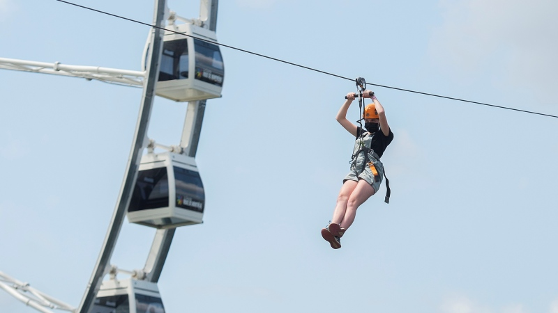A person is shown on a Zipline in the Old Port in Montreal, Sunday July 25, 2021, as the COVID-19 pandemic continues in Canada and around the world. THE CANADIAN PRESS/Graham Hughes