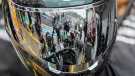 Technicians are reflected in a helmet during work on the car of Mercedes driver Valtteri Bottas at the Sochi Autodrom circuit, in Sochi, Russia, on Sept. 23, 2021. (Sergei Grits / AP)
