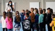 A teacher speaks to students returning to a primary school in Belegis, Serbia, on Sept. 1, 2021. (Darko Vojinovic / AP)
