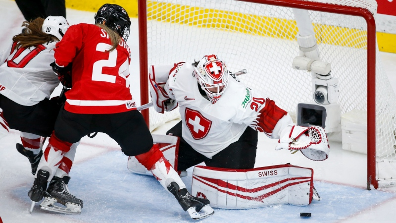 Switzerland's goalie Andrea Braendli, right, grabs for the puck as Canada's Natalie Spooner looks on during third period semi-final IIHF Women's World Championship hockey action in Calgary, Alta., Monday, Aug. 30, 2021. (THE CANADIAN PRESS / Jeff McIntosh)