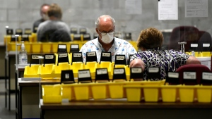 Workers prepare the bins with names of candidates into which special ballots from national, international, Canadian Forces and incarcerated electors will be counted and organized, at Elections Canada's distribution centre in Ottawa on election night of the 44th Canadian general election, on Monday, Sept. 20, 2021. (THE CANADIAN PRESS / Justin Tang)
