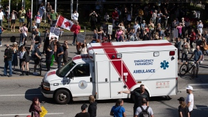 An ambulance passes through a crowd of people protesting COVID-19 vaccine passports and mandatory vaccinations for health-care workers, in Vancouver, on Wednesday, Sept. 1, 2021. (Darryl Dyck / THE CANADIAN PRESS)