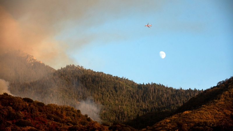 FILE - An air tanker prepares to drop retardant on the Windy Fire burning on Tule River Reservation in California on Thursday, Sept. 16, 2021. (AP Photo/Noah Berger)