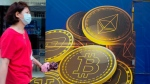 A woman walks past an advertisement for the Bitcoin cryptocurrency in Hong Kong, on June 1, 2021. (Vincent Yu / AP)
