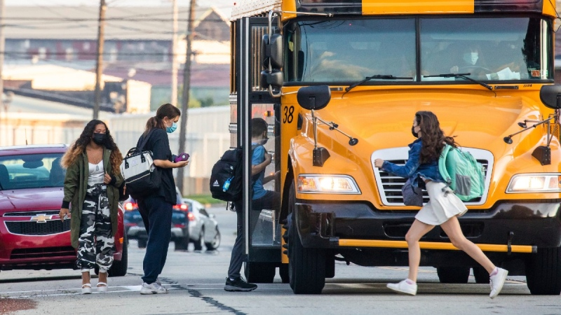 Students catch their bus near Ambridge Area Senior High School in Ambridge, Pa., on the first day of Pennsylvania's mask mandate for K-12 schools and day care centres on Sept. 7, 2021.  (Andrew Rush / Pittsburgh Post-Gazette via AP)