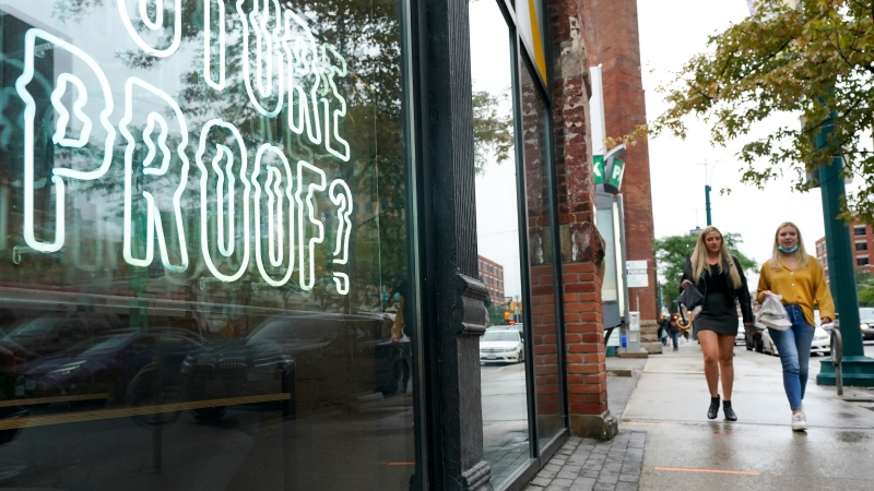 People walk past retail storefronts during the COVID-19 pandemic in Toronto on Wednesday, September 22, 2021. Ontario now requires proof of vaccination to enter many business across the province. THE CANADIAN PRESS/Nathan Denette