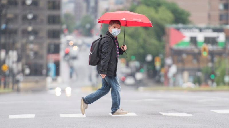 A man wears a face mask as he crosses a street in Montreal, Saturday, June 27, 2020, as the COVID-19 pandemic continues in Canada and around the world. THE CANADIAN PRESS/Graham Hughes