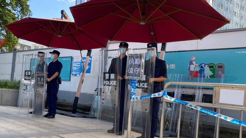 Chinese security guards stand behind shields on duty outside the Evergrande headquarters in Shenzhen, China, Friday, Sept. 24, 2021. (AP Photo/Ng Han Guan)