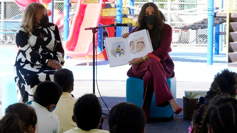"""Meghan, the Duchess of Sussex, reads from her book """"The Bench,"""" during her visit with Prince Harry, to P.S. 123, the Mahalia Jackson School, in New York's Harlem neighborhood, Friday, Sept. 24, 2021. At left is New York City School Chancellor Meisha Porter. (AP Photo/Richard Drew)"""