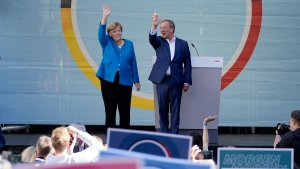 Chancellor Angela Merkel and Governor Armin Laschet, top candidate for the upcoming election, wave to supporters at the final election campaign event of the Christian Democratic Party, CDU, ahead of the German general election in Aachen, Germany, Saturday, Sept. 25, 2021. (AP Photo/Martin Meissner)