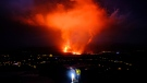 Two people walk as lava spews from a volcano on the Canary island of La Palma, Spain in the early hours of Saturday Sept. 25, 2021. (AP Photo/Daniel Roca)