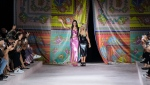 Dua Lipa, left, and Donatella Versace acknowledge applause at the conclusion of the Versace Spring Summer 2022 collection during Milan Fashion Week, in Milan, Italy, Friday, Sept. 24, 2021. (AP Photo/Luca Bruno)