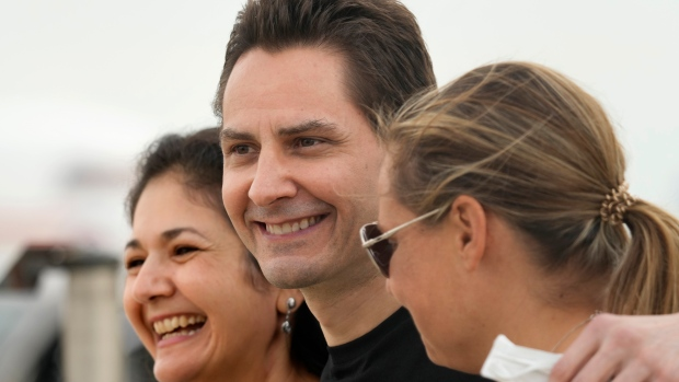 Michael Kovrig, centre, embraces his wife Vina Nadjibulla, left, and sister Ariana Botha after arriving at Pearson International Airport in Toronto, Saturday, Sept. 25, 2021. THE CANADIAN PRESS/Jeff McIntos