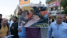 A Palestinian protester shows a picture of Osama Soboh, who was killed during clashes surrounding an Israeli army arrest in the northern village of Burqin, during a rally protesting the army operation, in the West Bank city Ramallah, Sunday, Sept. 26, 2021. (AP Photo/Nasser Nasser)