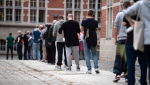 People queue to cast their ballots outside the Jane Addams School in Friedrichshain, Germany, Sunday, Sept. 26, 2021. German voters are choosing a new parliament in an election that will determine who succeeds Chancellor Angela Merkel after her 16 years at the helm of Europe's biggest economy. (Bernd von Jutrczenka/dpa via AP)