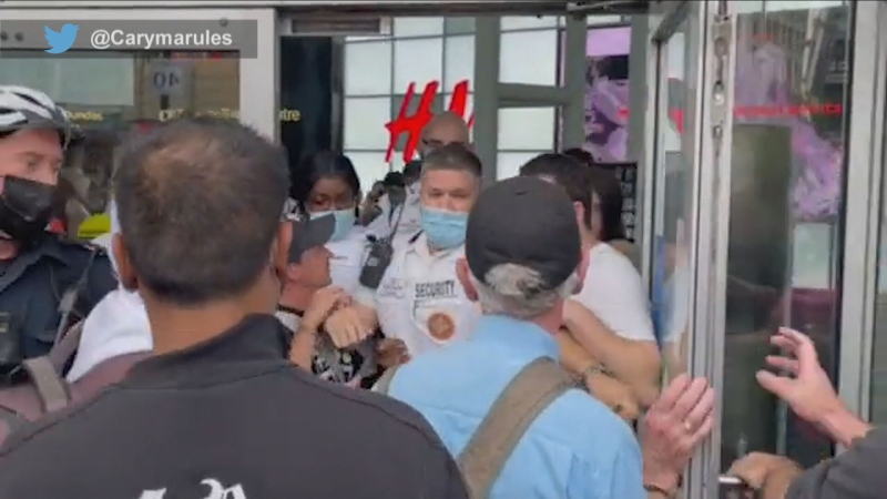 Security guards try to hold back anti-vaccination protesters from entering the Eaton Centre on Saturday. (Twitter/@Carymarules)