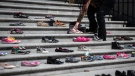 A woman places one of 215 pairs of children's shoes on the steps of the Vancouver Art Gallery as a memorial to the 215 children whose remains have been found buried at the site of a former residential school in Kamloops, in Vancouver, B.C., Friday, May 28, 2021. THE CANADIAN PRESS/Darryl Dyck