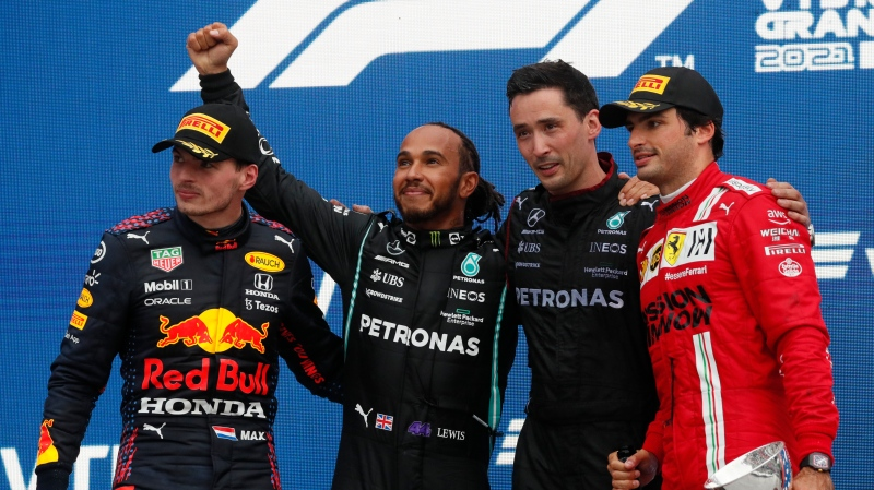 Mercedes driver Lewis Hamilton of Britain, second right, celebrates on the podium after winning the race alongside second place Red Bull's Max Verstappen and third place Ferrari's Carlos Sainz Jr. during the Russian Formula One Grand Prix at the Sochi Autodrom circuit, in Sochi, Russia, Sunday, Sept. 26, 2021. (Yuri Kochetkov/Pool Photo via AP)