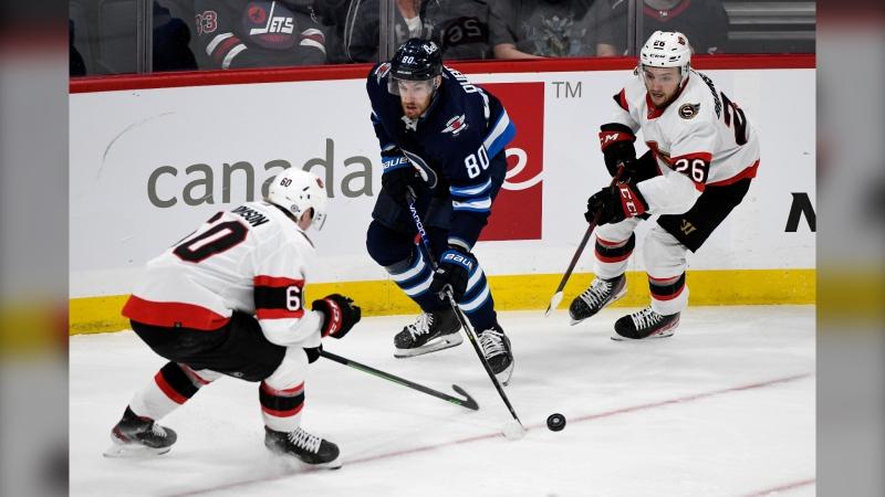 Winnipeg Jets' Pierre-Luc Dubois (80) carries the puck around Ottawa Senators' Lassi Thomson (60) and Erik Brannstrom (26) during third period NHL preseason action in Winnipeg, Sunday, Sept. 26, 2021. THE CANADIAN PRESS/Fred Greenslade