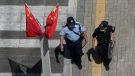 A policeman, right, and security guard walk past Chinese flags outside the Evergrande headquarters in Shenzhen, China, Friday, Sept. 24, 2021. (AP Photo/Ng Han Guan)