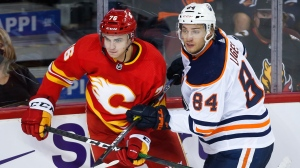 Edmonton Oilers' William Lagesson, right, checks Calgary Flames' Martin Pospisil during third period preseason NHL hockey action in Calgary, Alta., Sunday, Sept. 26, 2021. (THE CANADIAN PRESS/Jeff McIntosh )
