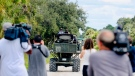 Members of the media film law enforcement as they drive swamp buggies down a dirt road on the Southside of the Carlton Reserve, while searching for any signs of Brian Laundrie, Tuesday, Sept. 21, 2021, in Venice, Fla. (Andrea Melendez/Naples Daily News via AP)