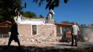 Residents pass next to a damaged Greek Orthodox chapel after a strong earthquake in Arcalochori village on the southern island of Crete, Greece, Monday, Sept. 27, 2021. (AP Photo/Harry Nikos)