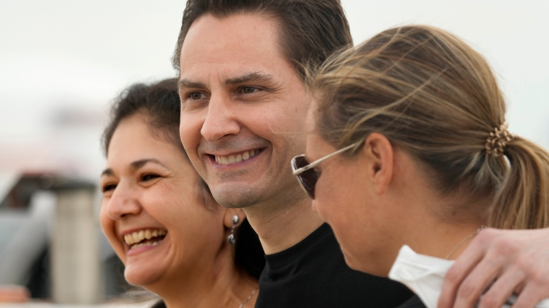 In this Sept. 25, 2021, file photo, Michael Kovrig, center, embraces his wife Vina Nadjibulla, left, and sister Ariana Botha after arriving at Pearson International Airport in Toronto. (Frank Gunn/The Canadian Press via AP)