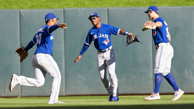 Toronto Blue Jays outfielders Teoscar Hernandez (37), Jarrod Dyson, center, and Randal Grichuk (15) celebrate after defeating the Minnesota Twins in a baseball game, Sunday, Sept. 26, 2021, in St. Paul, Minn. (AP Photo/Andy Clayton-King)
